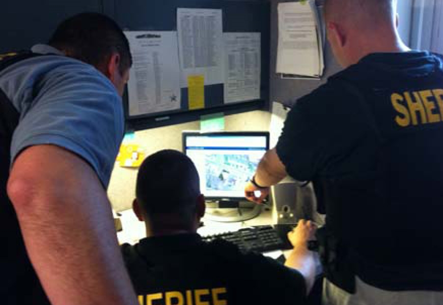 Officers gathered around a computer
