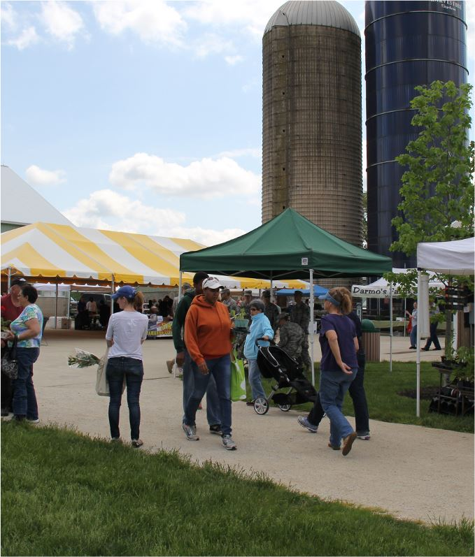 People walk around tents and displays with two silos in the background